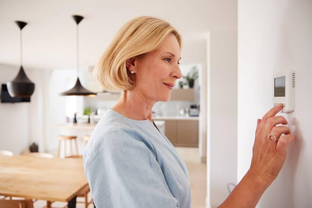 woman adjusting heating on wall